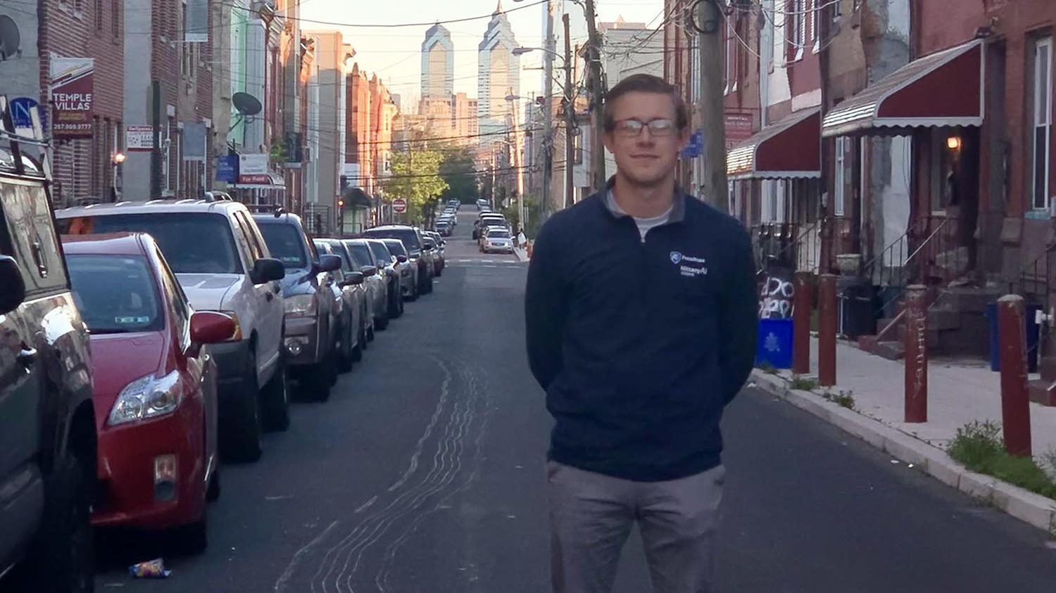 A man with light brown hair and glasses in a dark blue long sleeved shirt, gray pants and white sneakers is standing in the middle of the street with the Philadelphia city skyline in the background and parked cars on the left